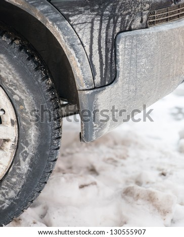 dirty car wheel stands on winter snowy road - stock photo