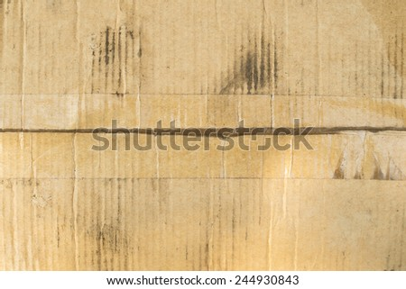 dirty cardboard box with clear adhesive tape - stock photo