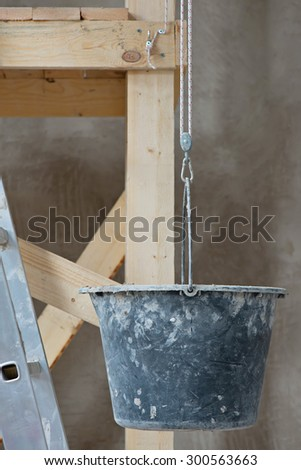 Dirty dark bucket and ladder on wall background. Conceptual photo of repairing works in room - stock photo