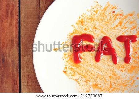 Dirty dishes from oil and Text,The idea is to eat foods that contain too much fat makes us fat. - stock photo