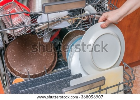 Dirty dishes in dishwasher and female hand. - stock photo