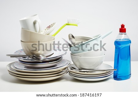 Dirty dishes pile needing washing up. Household chore concept on white background - stock photo