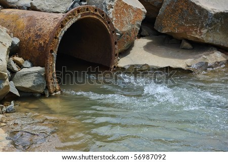 Dirty drain polluting a river. This pollutan comes from factory - stock photo