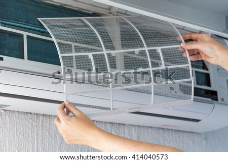 Dirty filter of air conditioner in female hands. Cleaning and washing maintenance - stock photo