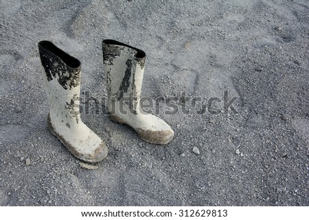 Dirty galoshes (rubber boots) at a construction site. - stock photo
