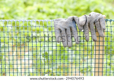 Dirty garden gloves on a plastic fence, gardening concept, shallow depth of field. - stock photo
