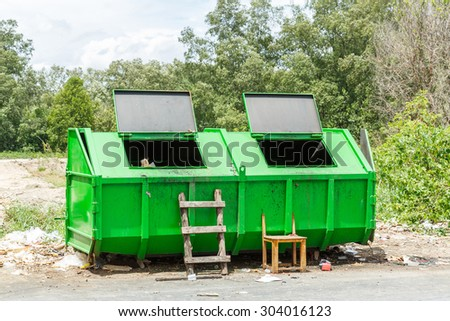 Dirty green color public bin with small ladder and broken wooden chair - stock photo