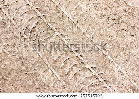 Dirty grunge tyre track on wet sand texture  - stock photo