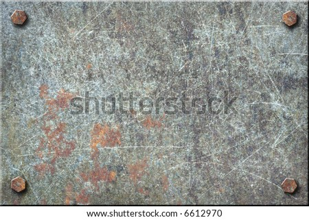 Dirty, heavily scratched metal plate with bolts. - stock photo