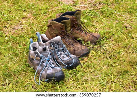 Dirty Hiking Boots on Wet Grass / Two pairs of hiking boots in a meadow of wet grass - stock photo