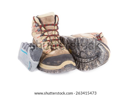 Dirty hiking boots with hiking socks isolated on white background. - stock photo