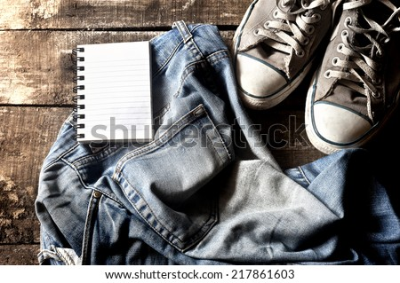 Dirty jeans with notepad in the pocket thrown on floor with a pair of sneakers - stock photo
