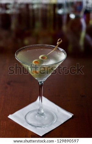 dirty martini chilled and served on a busy bar top with a shallow depth of field and color lights and glasses in the background - stock photo