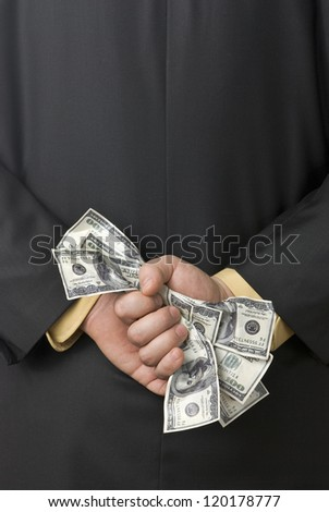 Dirty money grasped by a business man behind his back - stock photo