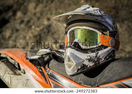 Dirty motorcycle motocross helmet with goggles - stock photo