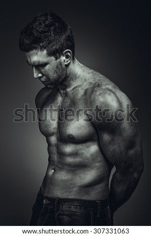 Dirty muscle man in pose on BW photo - stock photo