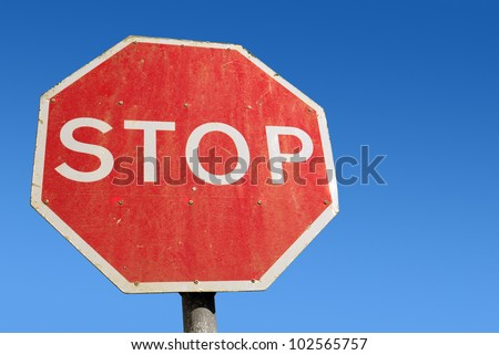 Dirty old red British Stop sign and blue sky. - stock photo