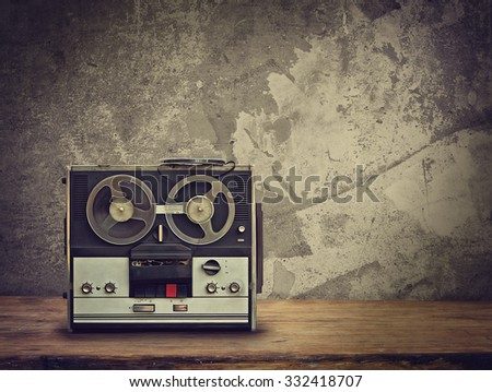 dirty old reel tape recorder on the wooden table. Retro toned - stock photo