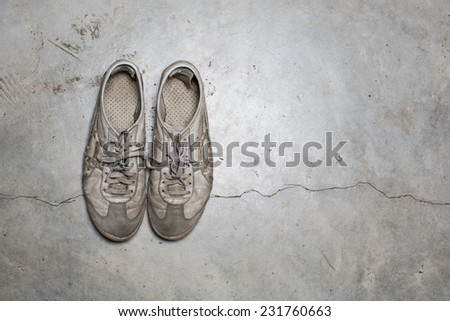 Dirty old shoes on concrete floor - stock photo