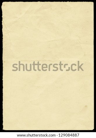 Dirty old yellowing piece of torn paper on black. - stock photo