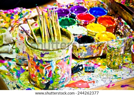 dirty paintbrush inside water container on the table - stock photo
