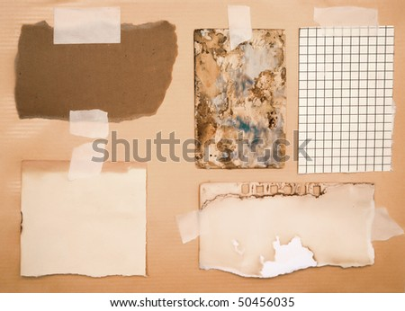 dirty pieces of paper over brown cardboard background - stock photo