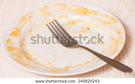 Dirty plate on the table. sauce smeared on a plate. - stock photo