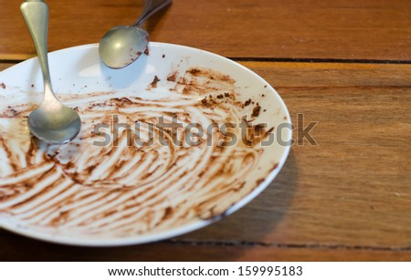 Dirty plate with spoon on wood table - stock photo