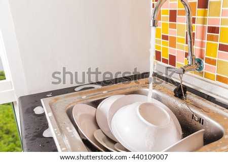 Dirty Plates and dishes in the sink - stock photo