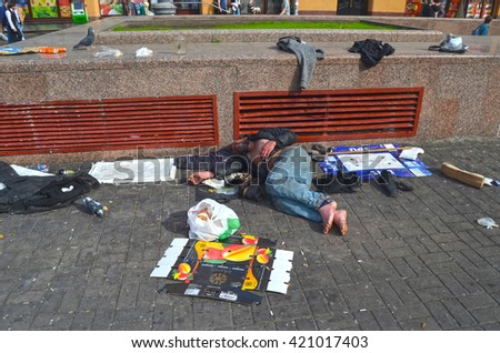 Dirty poor homeless man sleeps on Khreshatik - central street of Kiev.At April 8,2016 in Kiev, Ukraine - stock photo