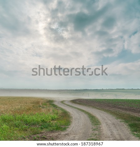 dirty road with dust and dramatic sky over it - stock photo