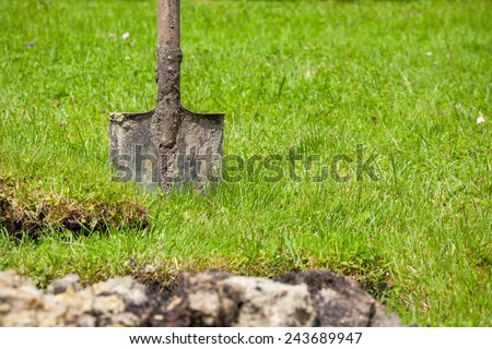 Dirty spade stuck in the soil  - stock photo