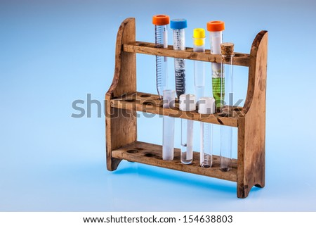 dirty test tobes in a rack over a blue background - stock photo