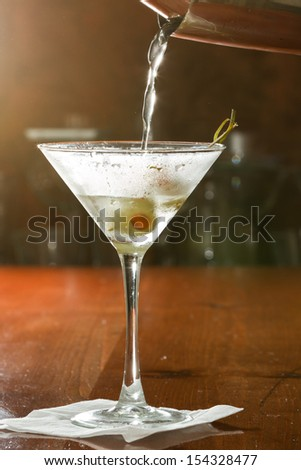 dirty vodka martini splashing into a cocktail glass with green olives - stock photo