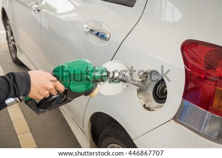 Dirty white car refueling on a gas station. - stock photo