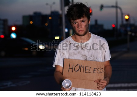 Dirty young homeless guy asking for help, sitting on a street - stock photo