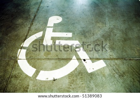 Disability icon on grunge background, floor of underground garage - stock photo