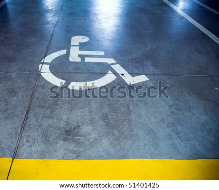 Disability sign in parking garage, underground interior - stock photo