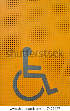 Disability sign on orange metal background - stock photo