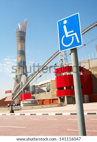 disabled access sign outside Khalifa sports stadium in Doha, Qatar, Middle East, where the 2006 Asian games were hosted  (wide angle lens distortion on edges) - stock photo