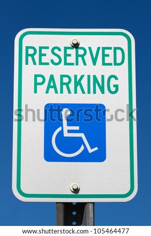 Disabled and handicapped reserved parking sign against a blue sky. - stock photo