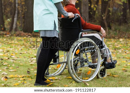Disabled and nurse on a walk in park - stock photo
