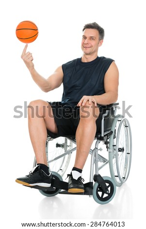 Disabled Basketball Player On Wheelchair Spinning Ball On His Finger Over White Background - stock photo