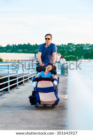 Disabled biracial child in wheelchair outdoors by lake with family. he has cerebral palsy. - stock photo