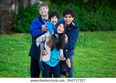 Disabled biracial child riding piggy back on his sister, family surrounding him, together at park. - stock photo