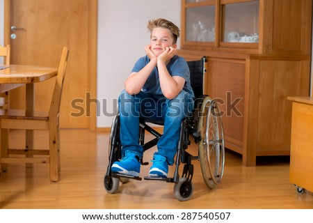 disabled boy in wheelchair at home in the living room - stock photo