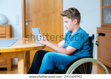 disabled boy in wheelchair chatting in the internet with tablet PC - stock photo