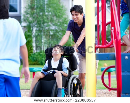 Disabled boy in wheelchair enjoying watching friends play at park on jungle gym - stock photo