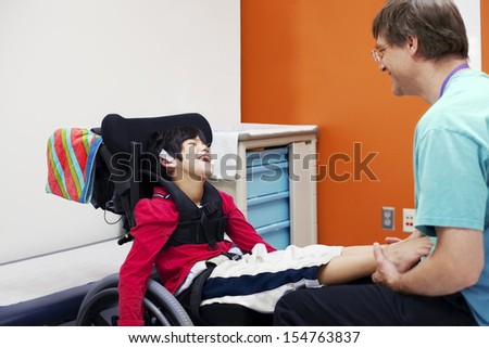 Disabled boy in wheelchair sharing laugh with his doctor or therapist - stock photo