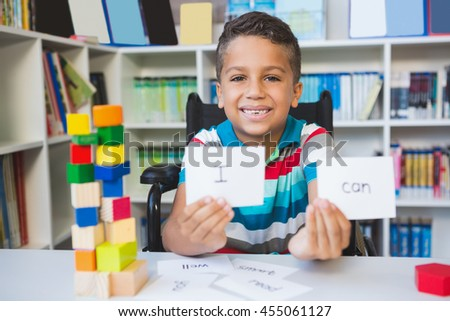 Disabled boy showing placard that reads I Can in library at school - stock photo